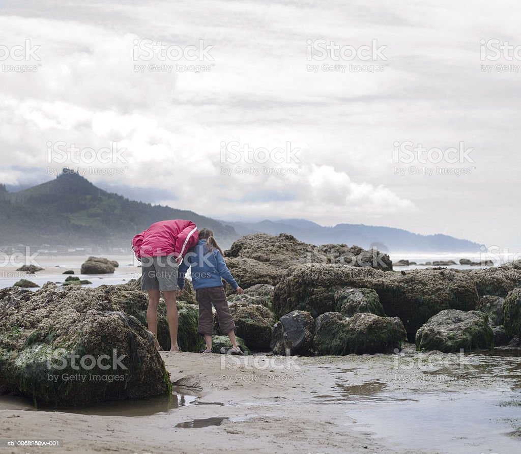 Father with daughter (8-9) by rocks on beach royalty-free stock photo