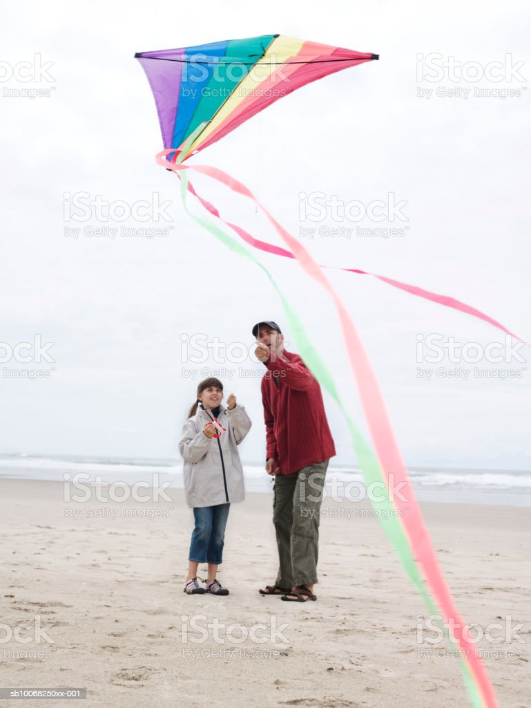 Father with daughter (8-9) flying kite on beach royalty-free stock photo