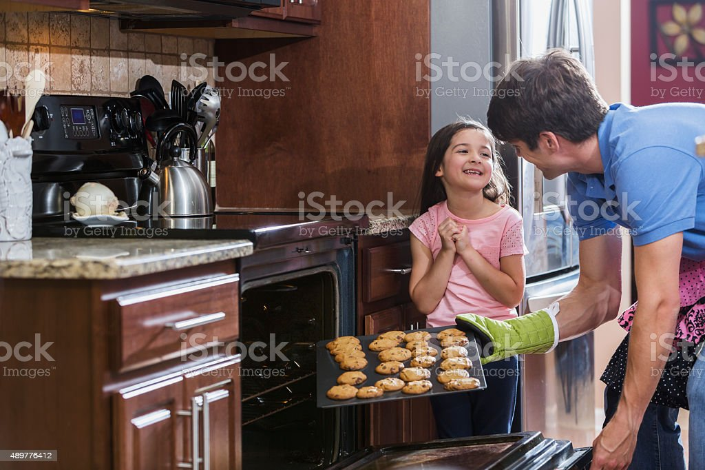 Father with daughter in kitchen baking cookies stock photo