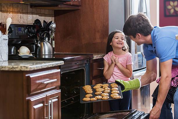 vater mit tochter in der küche backen kekse - sanft und sorgfältig stock-fotos und bilder