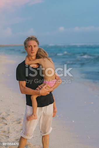 929671306 istock photo Father with daughter  walking on the beach in Bali 931554470