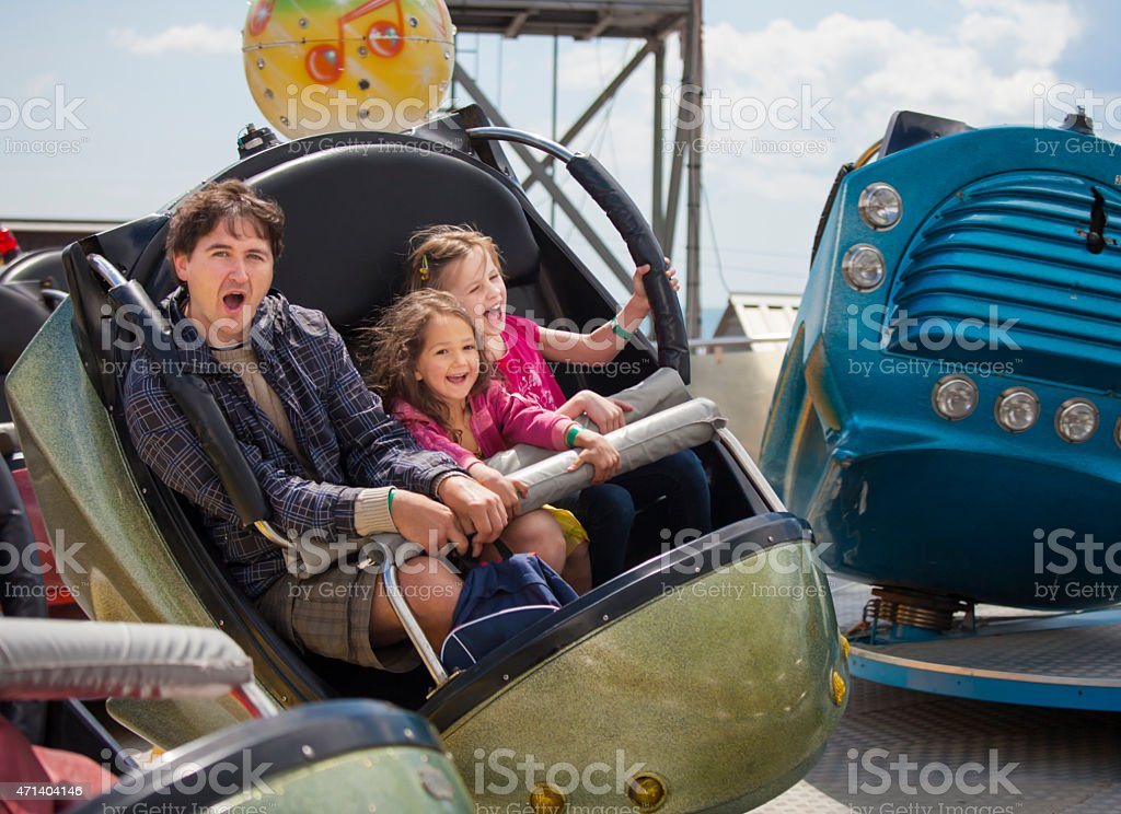 Father with daughters in the amusement park stock photo