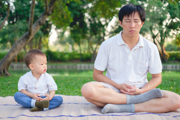 Father with eyes closed and Cute little Asian 18 months / 1 year old toddler baby boy child practices yoga & meditating outdoors on nature stock photo