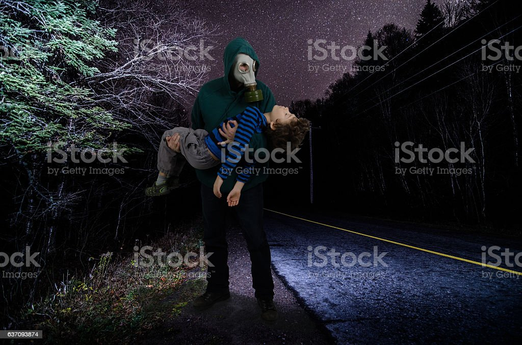Father with gas mask holding his dead son on street stock photo