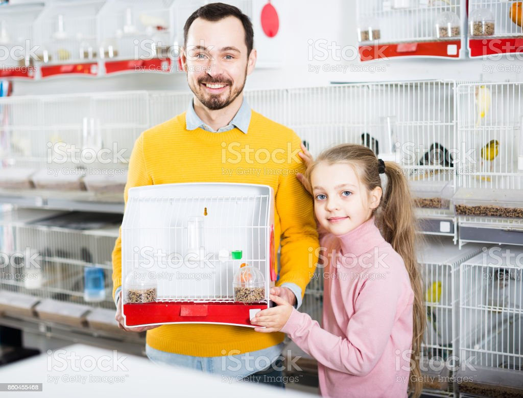 Father with girl acquired the canary and bird cage stock photo