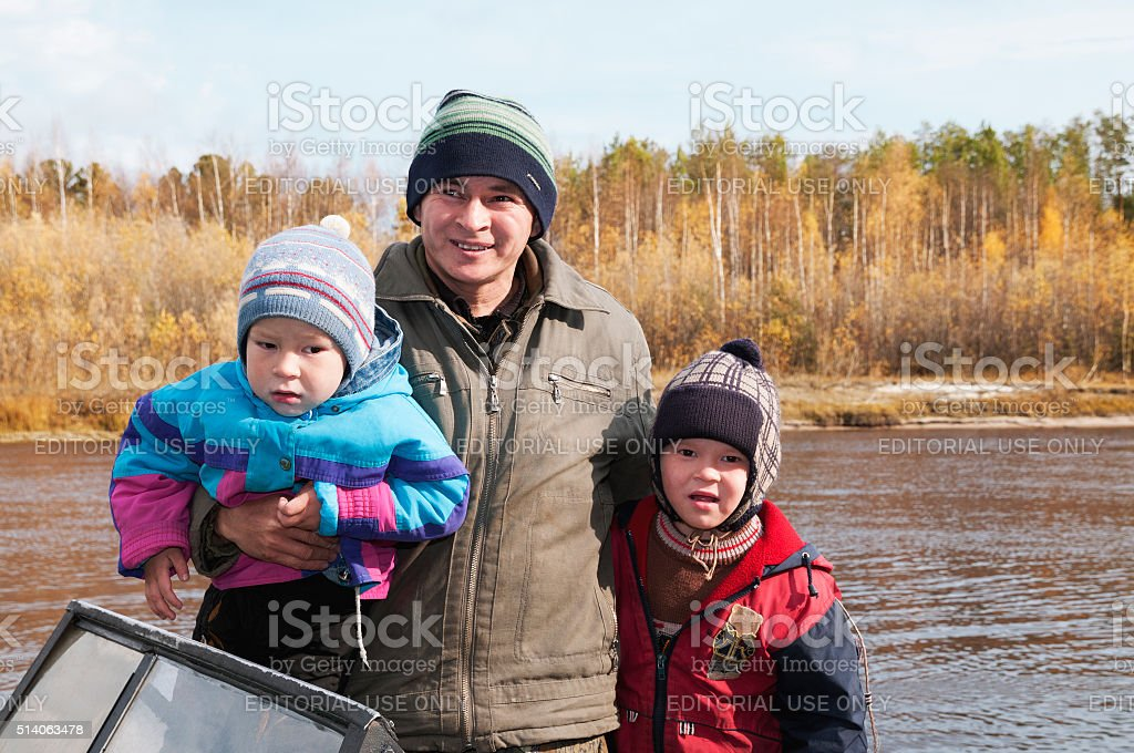 Father with his children in a boat on a river stock photo