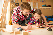 Father with his cute little daughter in wood shop working on a project. Making something out of wood. Girl is happy to help. Wearing similar plaid shirts. Caucasian, day time. Lean in.