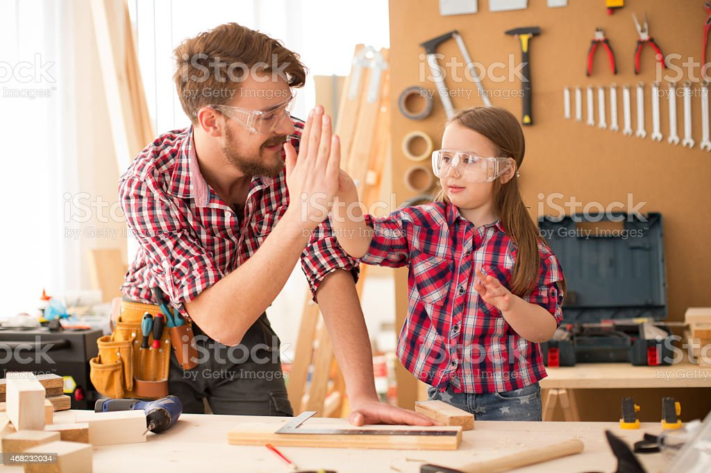 Father with his cute little daughter in woodshop. stock photo
