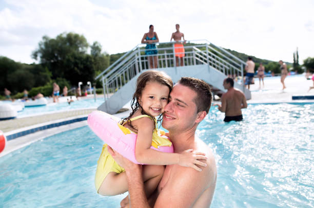 Father with his daughter in swimming pool. Sunny summer. stock photo