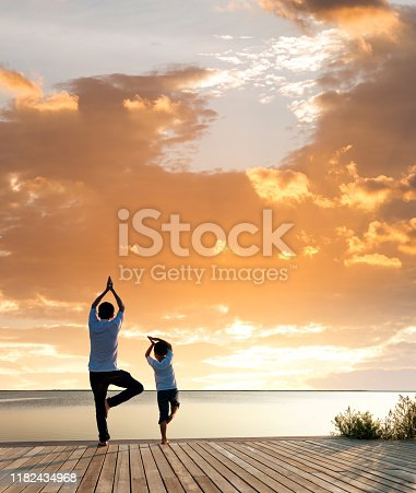 Father with his son doing yoga by the lake at sunset.