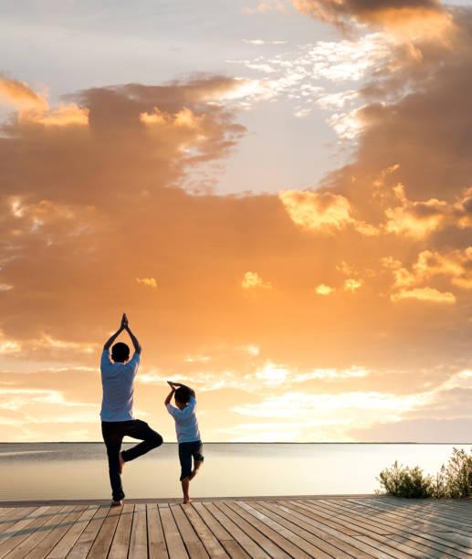 père avec son fils faisant le yoga par le lac au coucher du soleil - nuage 6 photos et images de collection