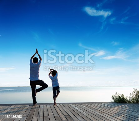 Father with his son doing yoga by the lake.