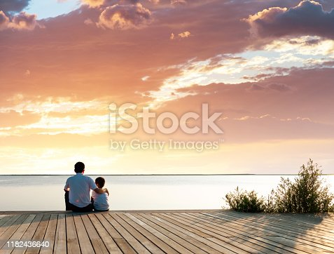 Father with his son enjoying lake view.