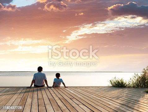 Father with his son enjoying lake view at sunset.