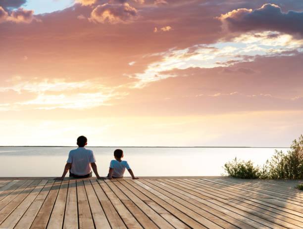 père avec son fils appréciant la vue de lac - nuage 6 photos et images de collection