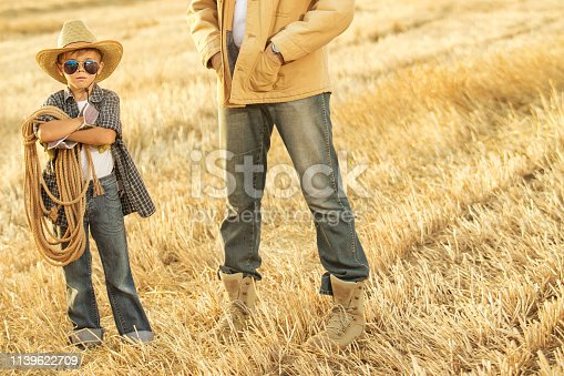 Father with his son on the field in cowboy hats, travel, vacation, summer, father day concept