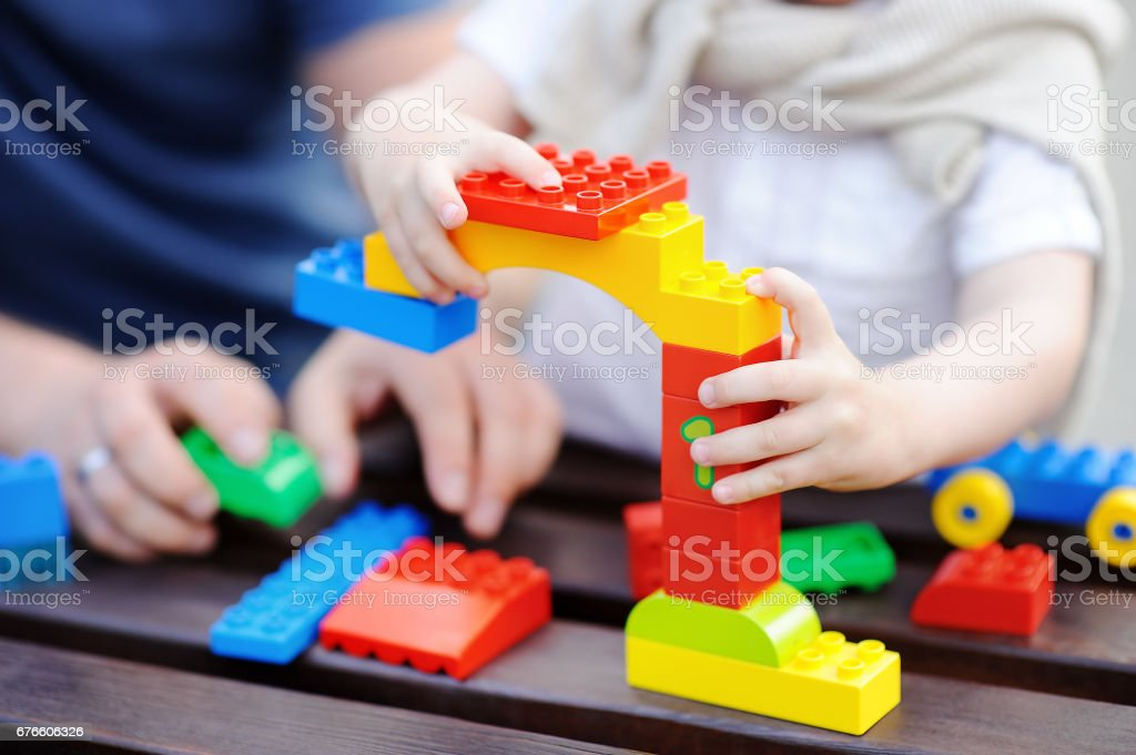 Father with his toddler son playing with colorful plastic blocks stock photo