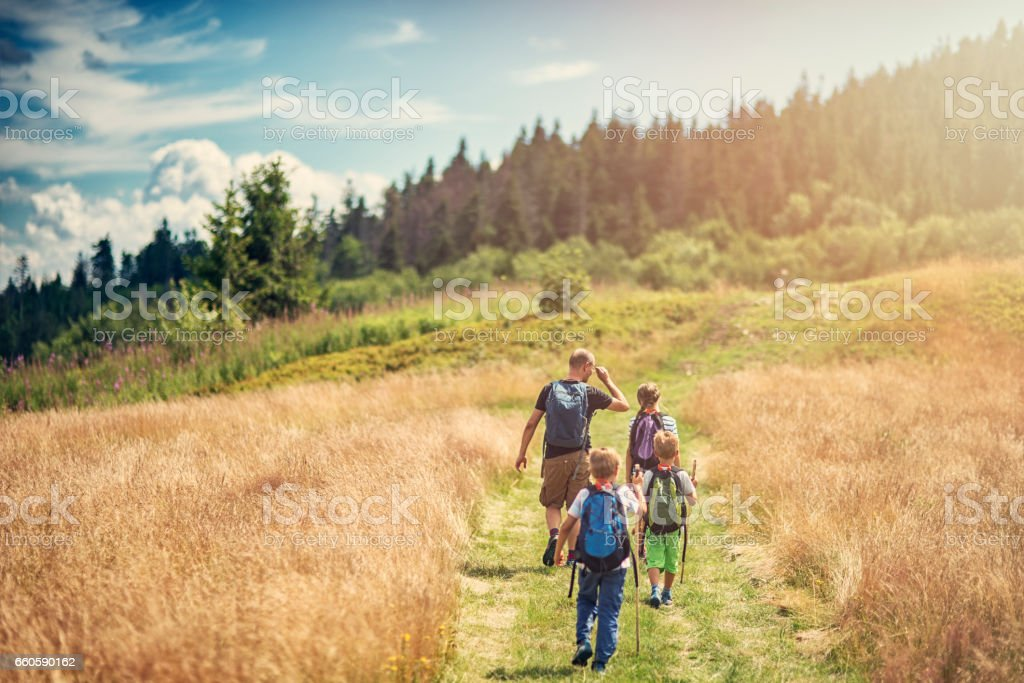 Father with kids hiking in beautiful nature stock photo