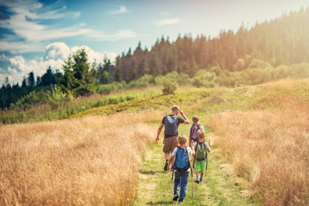 father with kids hiking in beautiful nature - hiking stock photos and pictures