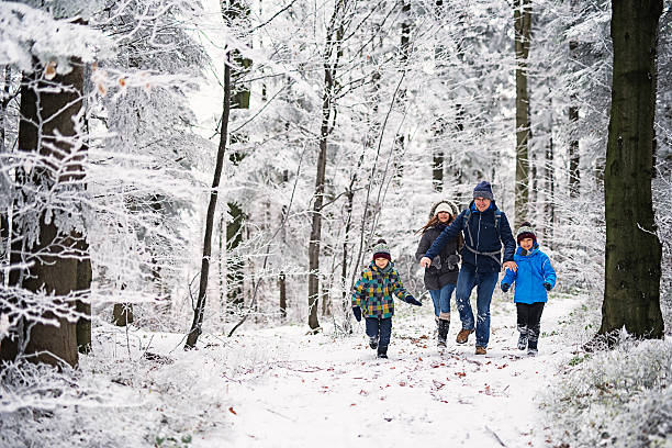 Father with kids running in beautiful winter forest stock photo