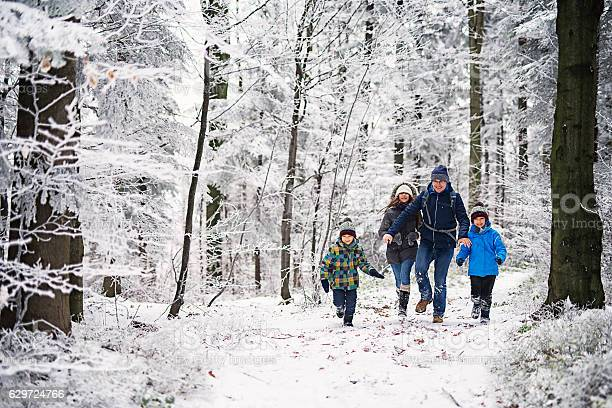 Photo of Father with kids running in beautiful winter forest