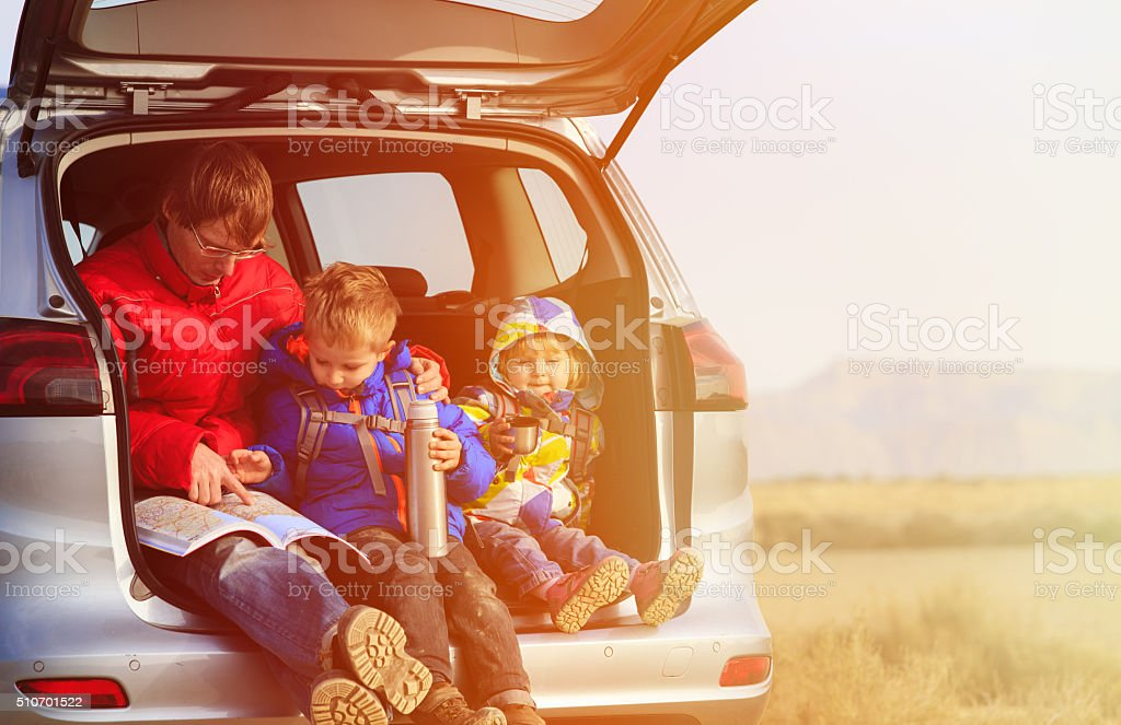 father with kids travel by car in mountains stock photo