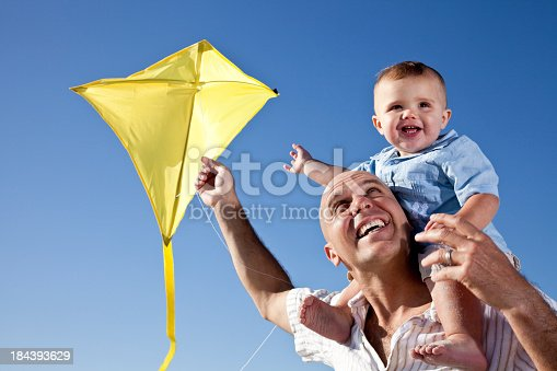 Father, 30s, and son, 15 months, flying a kite.