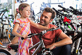 Father buying a bicycle for his little daughter in a bike store.