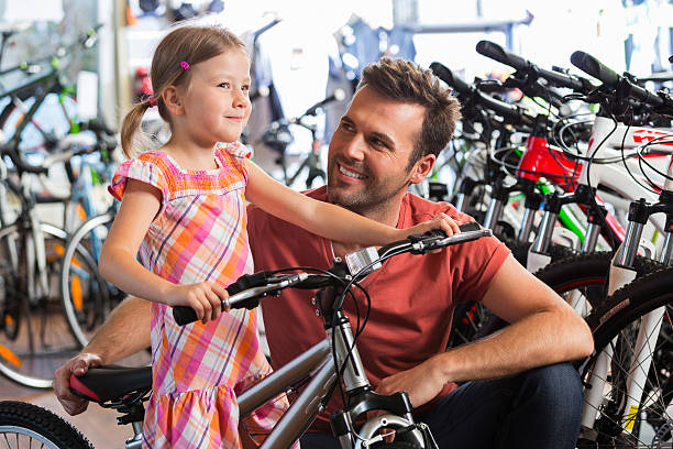 Father with little daughter in bike store Father buying a bicycle for his little daughter in a bike store. bicycle shop stock pictures, royalty-free photos & images