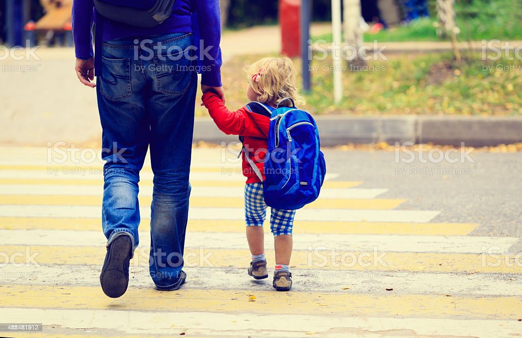 father with little daughter walking to school or daycare stock photo