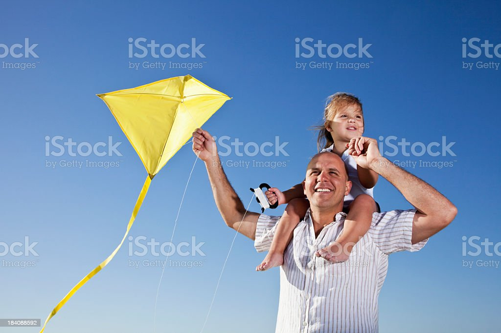 Father with little girl on shoulders flying kite royalty-free stock photo