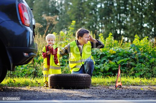 istock Father with little son repairing car and changing wheel together 610569932