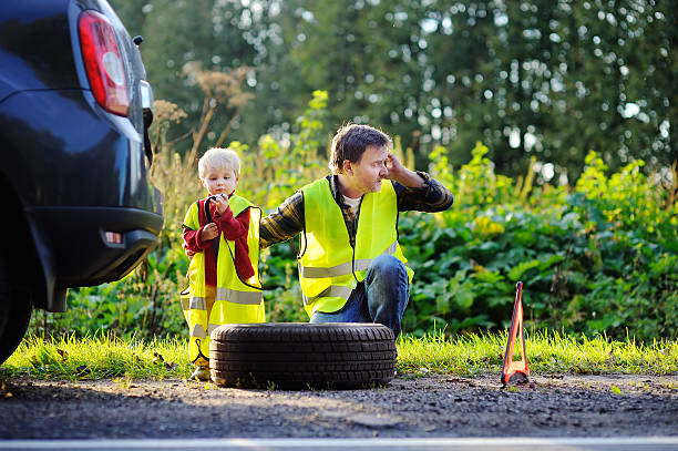 Father with little son repairing car and changing wheel together​​​ foto