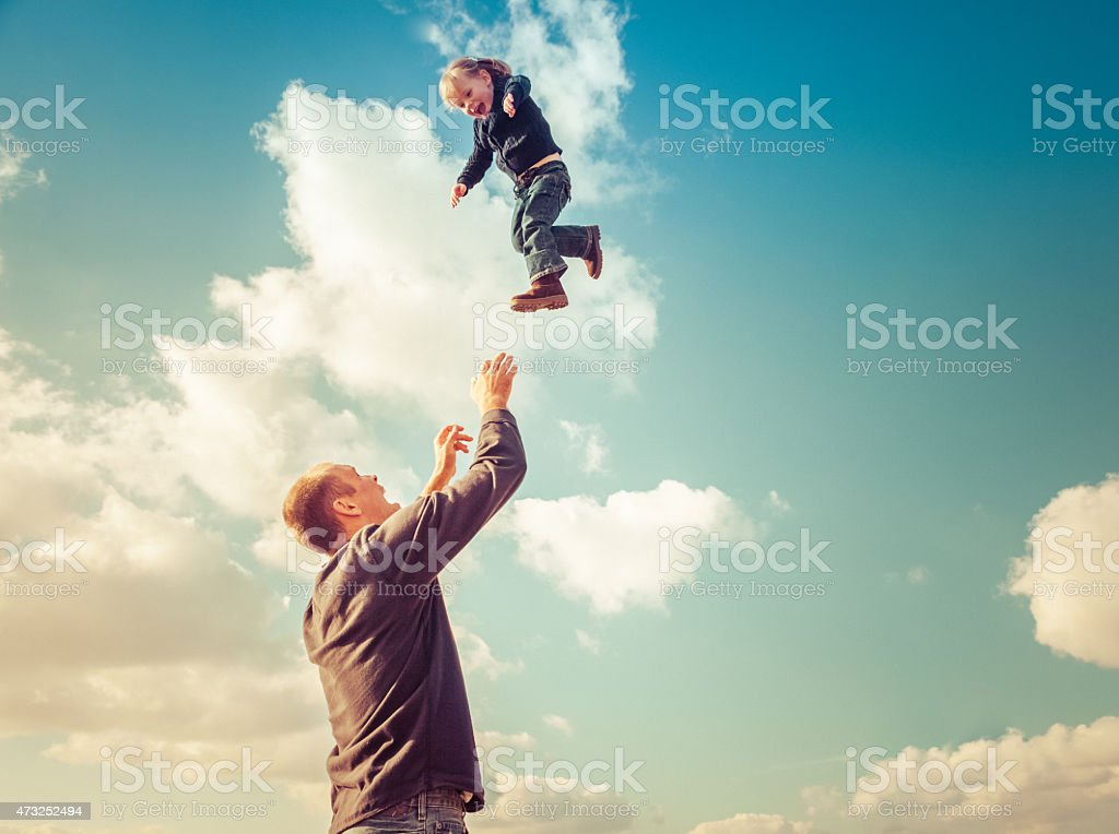 Father with raised arms catching young girl falling from sky stock photo