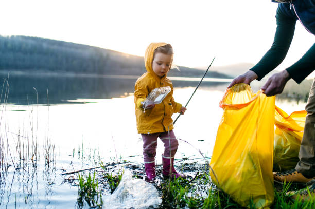 Father with small daughter collecting rubbish outdoors in nature, plogging concept. stock photo