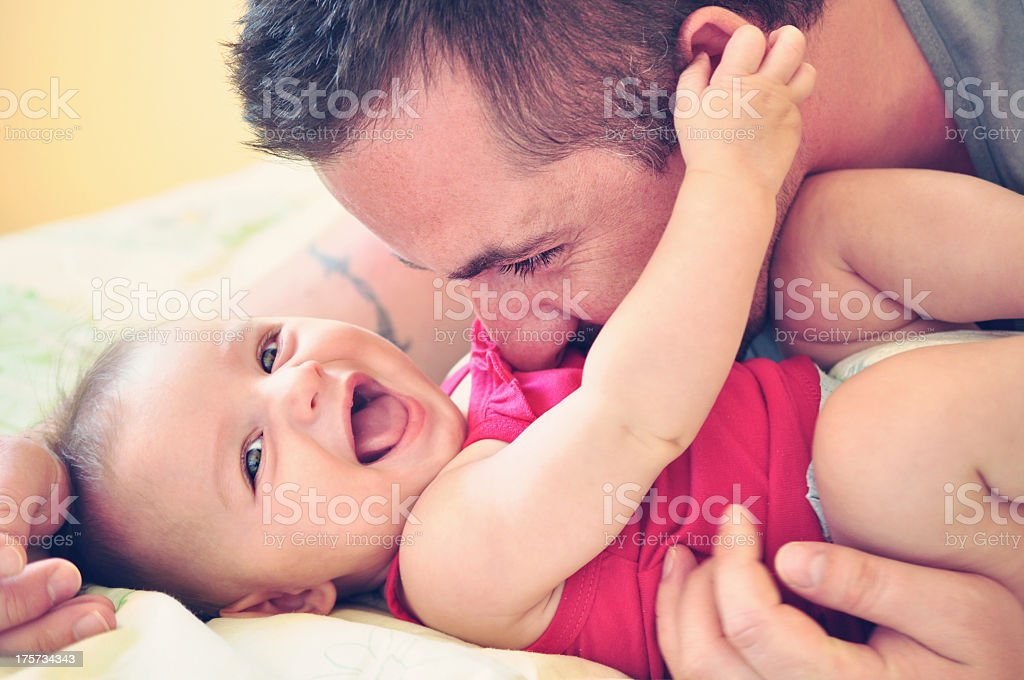 Father with smiling baby daughter dressed in red stock photo