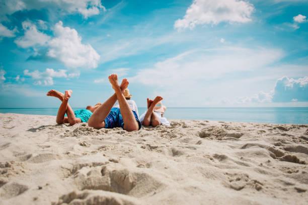 padre con hijo e hija relajarse en la playa - playa fotografías e imágenes de stock