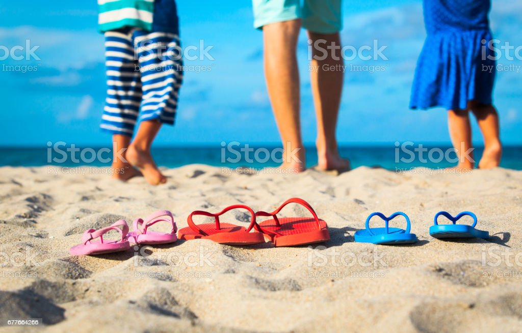 father with son and daughter walking at beach stock photo
