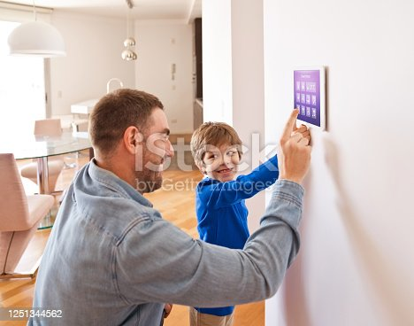 Father teaching his son controlling home with a digital touch screen panel. Concept of internet of things.