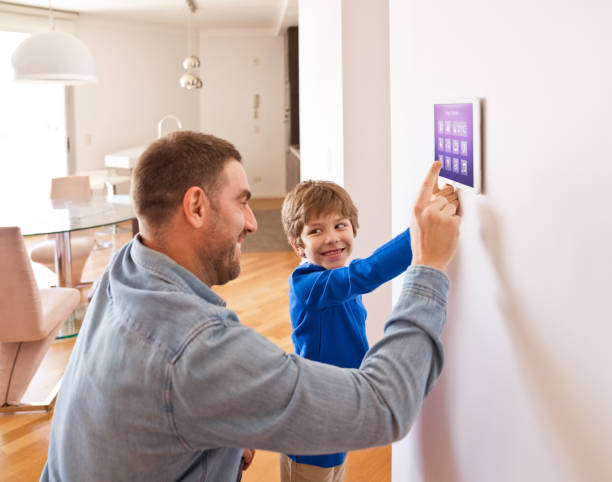 Father with son controlling smart devices with a digital tablet at home Father teaching his son controlling home with a digital touch screen panel. Concept of internet of things. smart thermostat stock pictures, royalty-free photos & images