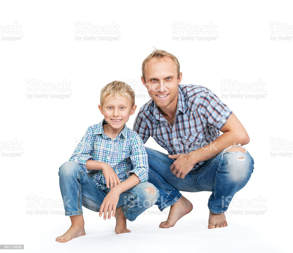 Father with son dressed in jeans and plaid shirts stock photo