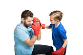Father with son during boxing training isolated on white
