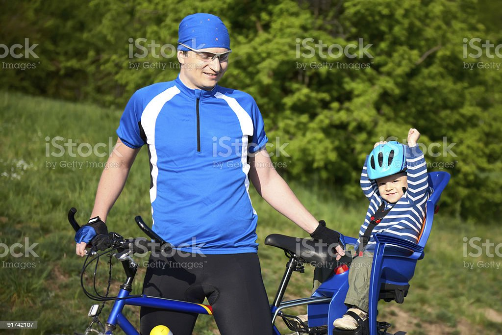father with son in bicycle chair stock photo