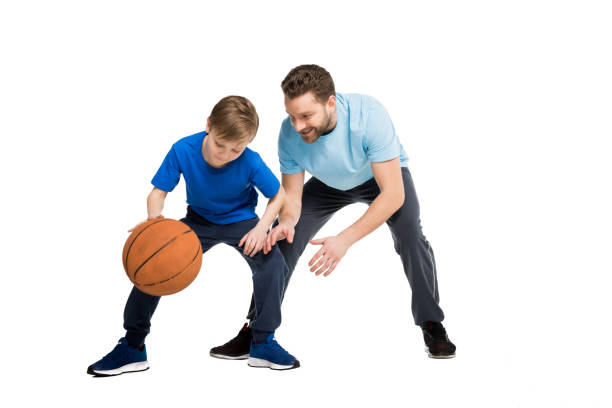 Father with son in casual clothes playing basketball isolated on white stock photo