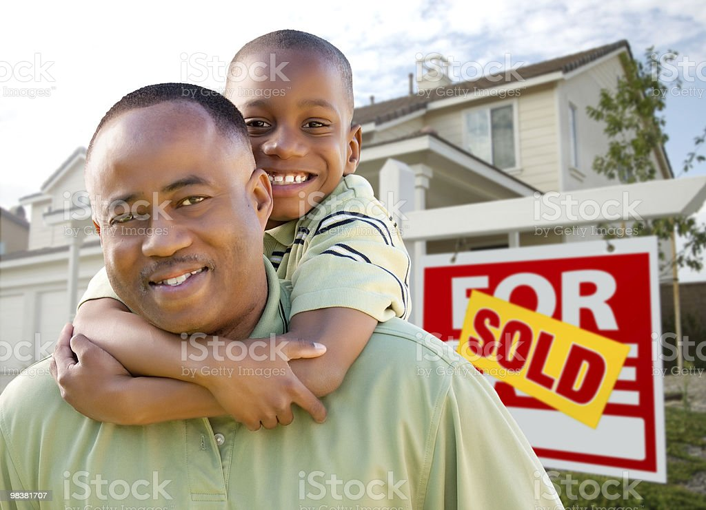 Father with Son In Front of Sold Sign and Home royalty-free stock photo