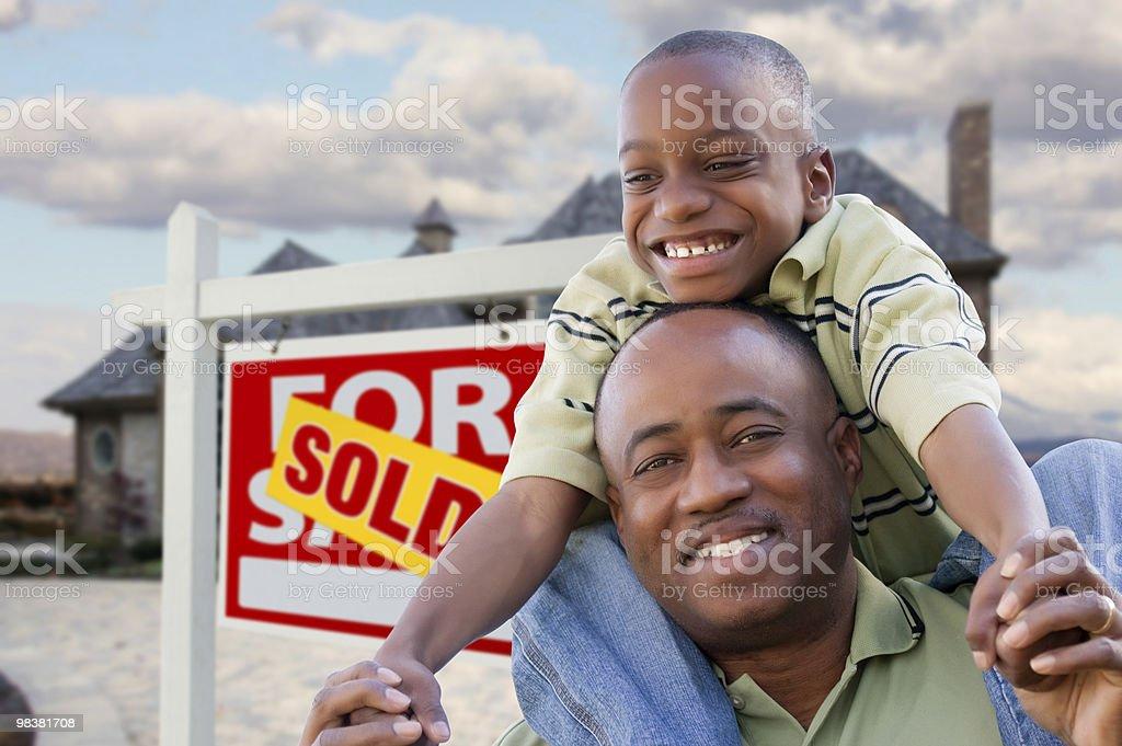 Padre con il figlio davanti al segno venduto e la casa foto stock royalty-free