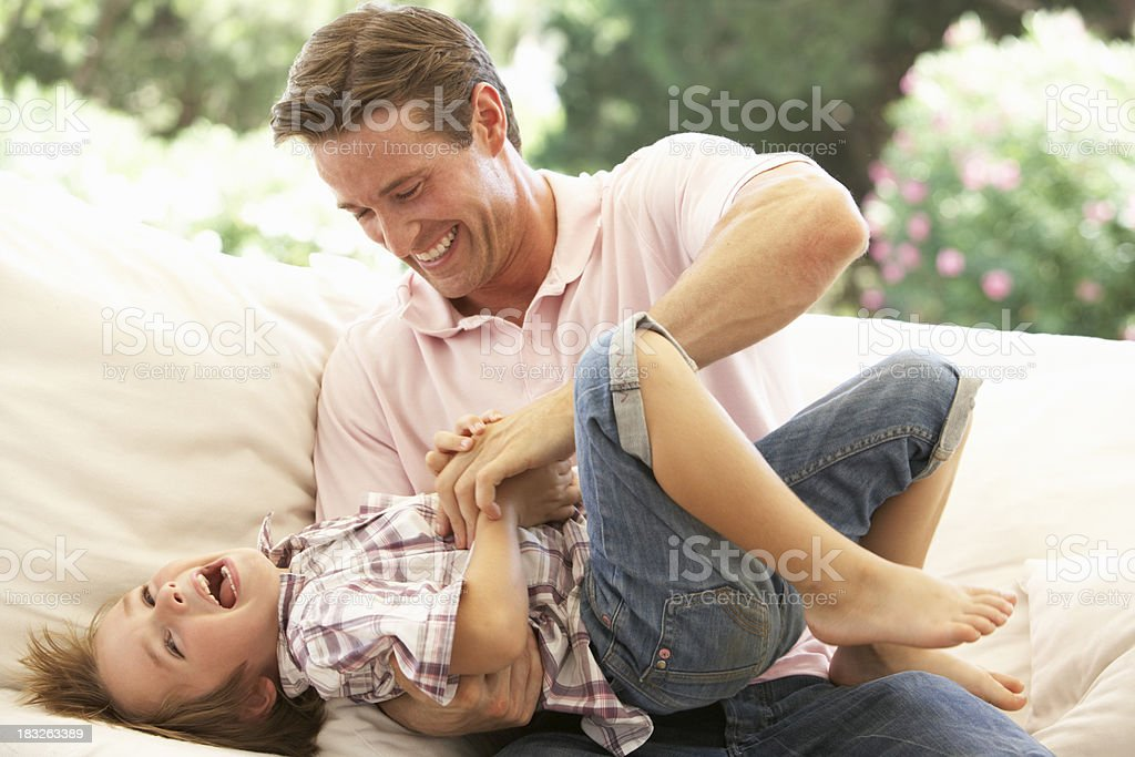 Father With Son Laughing On Sofa stock photo