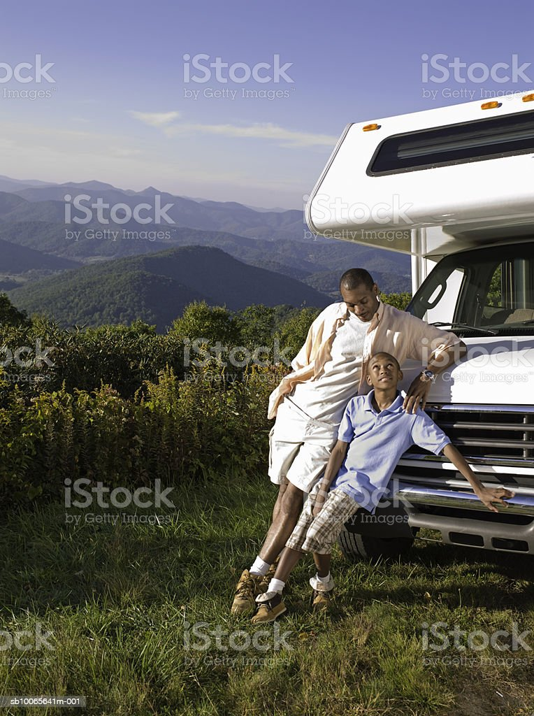 Father with son (12-13) leaning against motorhome foto de stock libre de derechos