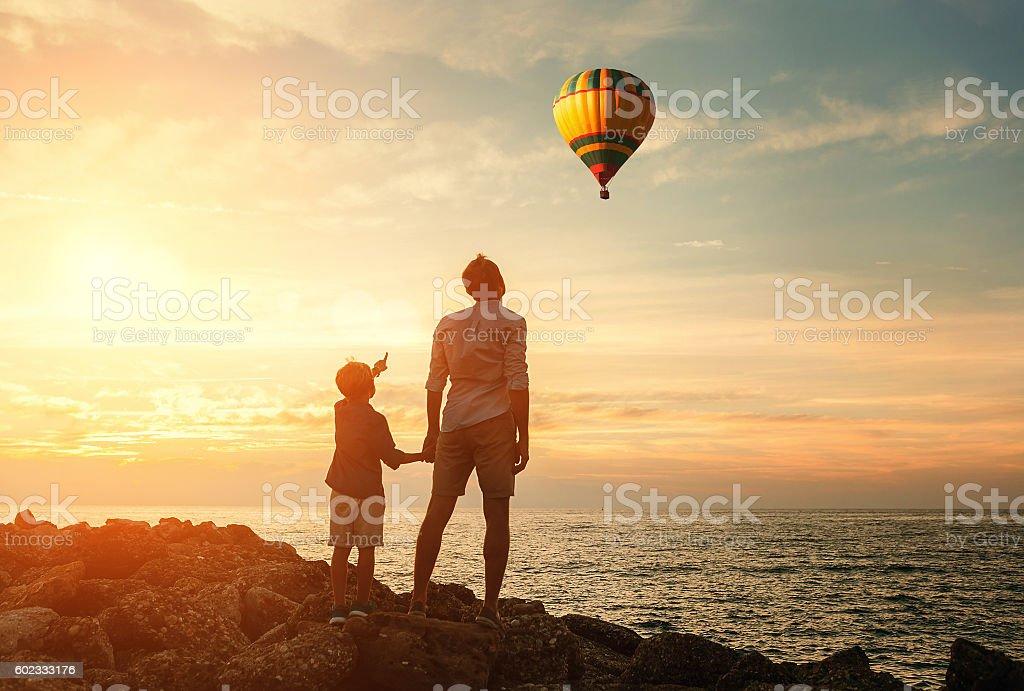 Père avec fils regard sur la ballon sur la côte de la mer - Photo