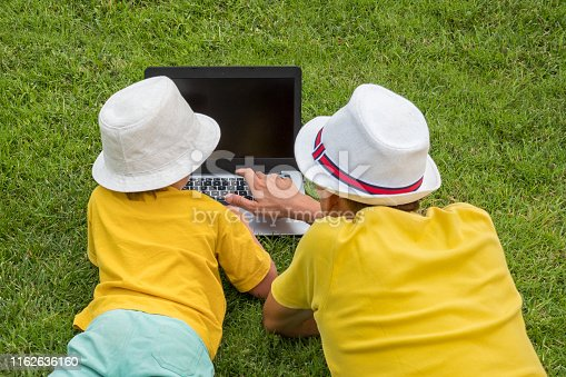 Father and son with notebook on sunny summer day. New approach to education. Back view of two boys with laptop lying on backyard. Happy summer sunny days. Boys in bright T-shirts spending time outdoor